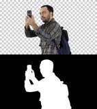 Attraktiv ung turist med ryggsäcken som går och använder mobiltelefonen, Alpha Channel royaltyfri fotografi
