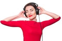 Attraktiv ung vuxen kvinna i röd kläder som lyssnar till musen Arkivbild