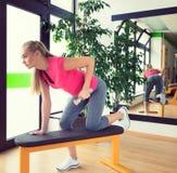 Attraktiv utbildning för ung kvinna i idrottshall med hantlar Royaltyfri Bild