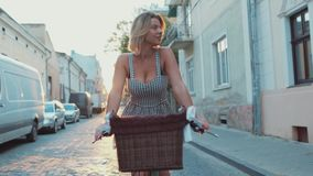 Attraktiv varm blond kvinna i en moderiktig klänning som rider tappningcykeln ner den öde stadsgatan i ett ljust stock video