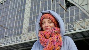 Attraktiv vuxen flicka i blått lag och färgrik hatt med halsduken som ler, medan vänta på järnvägsstationen under soligt arkivfilmer