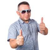 Attraktiv vuxen man med bärande solglasögon för skägg i gest för tumme för sommarskjortashower som övre isoleras på vit bakgrund Arkivbild