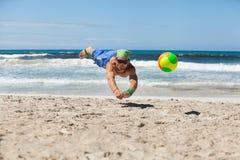 Attraktiv vuxen man som spelar strandvolleyboll i sommar Fotografering för Bildbyråer