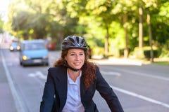 Attraktiv yrkesmässig kvinna som cyklar för att arbeta Arkivbilder
