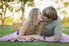 Attraktiva älska par som kysser i parkera arkivfoto