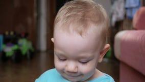 Attraktiva 2 åriga pojkeblickar på kameran och leendena och ändringsansiktsuttrycken Hem- inredningar blå skjorta t arkivfilmer