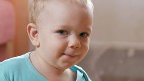 Attraktiva 2 åriga pojkeblickar på kameran och leendena och ändringsansiktsuttrycken Hem- inredningar blå skjorta t stock video