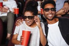 Attraktiva afro amerikanska par som håller ögonen på filmen 3D Royaltyfri Fotografi