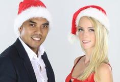Attraktiva blandade par som poserar för jul Royaltyfri Bild