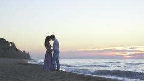 Attraktiva enloved barnpar har ett sött romantiskt ögonblick på stranden på aftonen Romantiskt bröllopsresabegrepp lager videofilmer