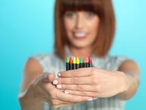 attraktiva färgrika crayons som rymmer kvinnan ung Arkivbild