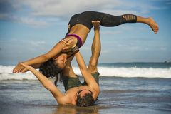 Attraktiva f?r det frialivsstilst?ende unga och koncentrerade par av yogaakrobater som ?va acroyogaj?mvikt och meditation royaltyfri foto