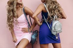 Attraktiva flickor i sexiga klänningar som poserar med öppnade munnar Arkivfoto
