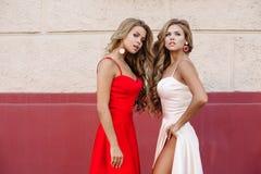 Attraktiva flickor i stilfulla klänningar som poserar på kameran Royaltyfria Bilder