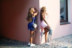 Attraktiva flickor som bär små klänningar och ryggsäckar för innehavstilblått Arkivbild