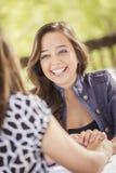 Attraktiva flickvänner som skrattar att sitta utanför Royaltyfria Foton