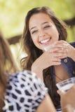 Attraktiva flickvänner som skrattar att sitta utanför Royaltyfri Foto