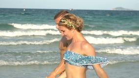 Attraktiva gladlynta par som går på stranden stock video