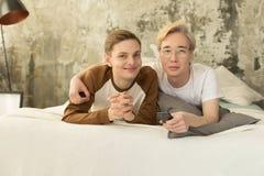 Attraktiva internationella homosexuella par som kopplar av i säng för nattsömn och ser kameran arkivfoto