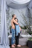 Attraktiva internationella par av mannen med den kala bröstkorgen som kramar H Arkivfoto