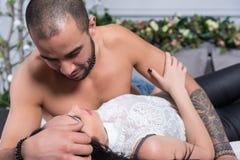 Attraktiva internationella par av mannen med den kala bröstkorgen som tatueras Arkivfoto