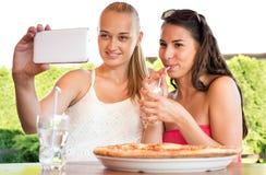 Attraktiva kvinnliga vänner som tar en selfie med smartphonen Arkivbild