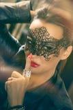 Attraktiva kvinnor med svart snör åt maskeringen royaltyfri fotografi