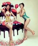 Attraktiva kvinnor som poserar nära den stora kakan Utvikningsbrudparti Congratulati Arkivbild