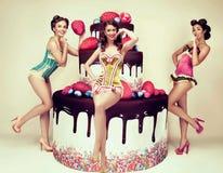 Attraktiva kvinnor som poserar nära den stora kakan Utvikningsbrudparti Congratulati Royaltyfri Bild