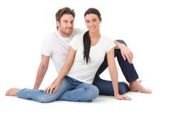 Attraktiva älska par som sitter på att le för golv Arkivbilder