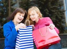 Attraktiva lyckliga kvinnor med shoppingpåsar shopping Arkivfoto