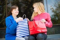 Attraktiva lyckliga kvinnor med shoppingpåsar shopping Fotografering för Bildbyråer