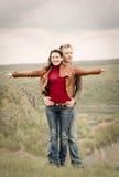 Attraktiva lyckliga par som poserar i vildmarken Royaltyfri Bild