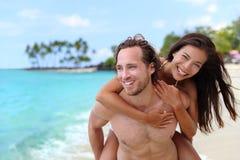 Attraktiva lyckliga par som skrattar ha strandgyckel Royaltyfri Fotografi