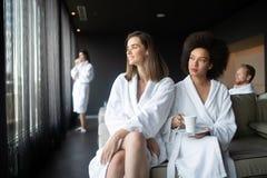 Attraktiva lyckliga unga kvinnor som dricker kaffe p? brunnsortmitten fotografering för bildbyråer