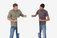 Attraktiva män som rymmer det tomma kortet och ser det Fotografering för Bildbyråer
