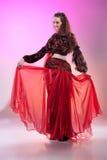 attraktiva magdansdansaredanser klär den östliga flickaorangen Arkivbild
