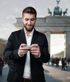Attraktiva manlekar med hans smarta telefon som är främst av den Brandenburger porten Royaltyfri Bild