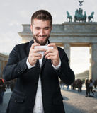 Attraktiva manlekar med hans smarta telefon som är främst av den Brandenburger porten Arkivfoto