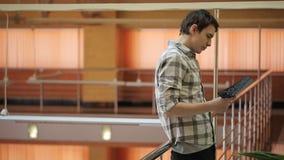 Attraktiva manställningar i korridoren som litar på metallräcket lager videofilmer