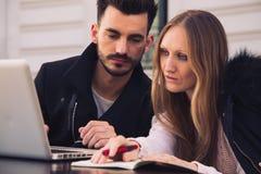 Attraktiva moderna par som utanför arbetar på bärbara datorn Arkivbild