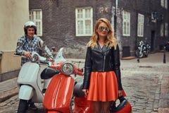Attraktiva par, en stilig man och sexigt kvinnligt anseende på en gammal gata med två retro sparkcyklar royaltyfria bilder