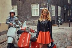 Attraktiva par, en stilig man och sexigt kvinnligt anseende på en gammal gata med två retro sparkcyklar royaltyfri fotografi