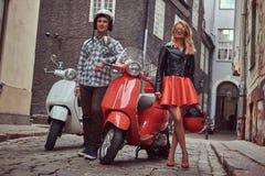 Attraktiva par, en stilig man och sexigt kvinnligt anseende på en gammal gata med två retro sparkcyklar arkivbilder