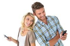 Attraktiva par genom att använda deras smartphones Royaltyfria Bilder