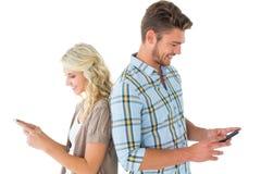 Attraktiva par genom att använda deras smartphones Royaltyfri Foto