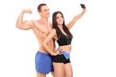 Attraktiva par i sportswearen som tar en selfie Fotografering för Bildbyråer