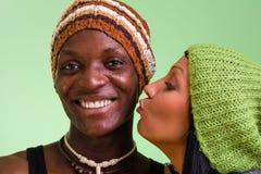 Attraktiva par i vinter danar locket som ler på kameran på gräsplan Royaltyfria Bilder