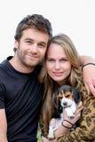 Attraktiva par med den älsklings- hunden för familj arkivfoto