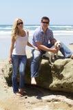 Attraktiva par med deras labradorvalp på stranden Royaltyfri Foto